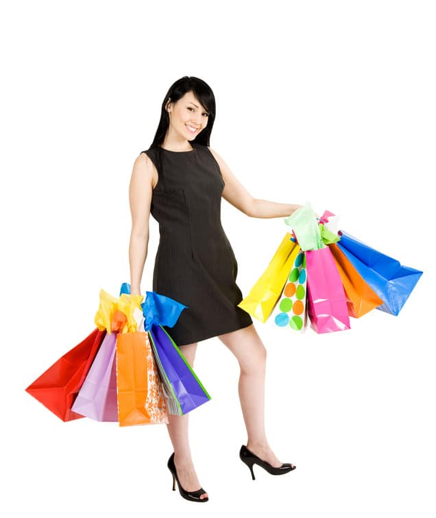 An isolated shot of a beautiful woman carrying shopping bags